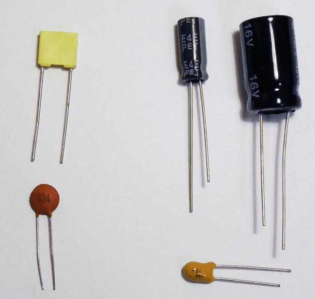 Po lewej: kondensatory bezbiegunowe (ceramiczny na górze, foliowy na dole) Po prawej: kondensatory biegunowe (elektrolityczne na górze, tantalowy na dole)