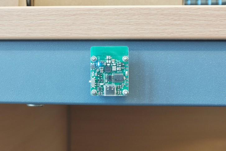 Nadajnik TX przyczepiony za pomocą magnesu do metalowego elementu stołu